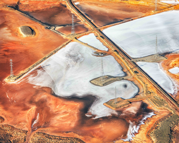 "© David Dahlenburg. 2019 AIPP SA Emerging Photographer of the Year. ""I was motivated to document the remnants surrounding the decommissioned Port Augusta coal fired power station before it was covered over with top soil to reduce airborne  pollution. This image was captured from a light plane. It depicts the human impact on the environment and the scars that are left behind from heavy industry."""