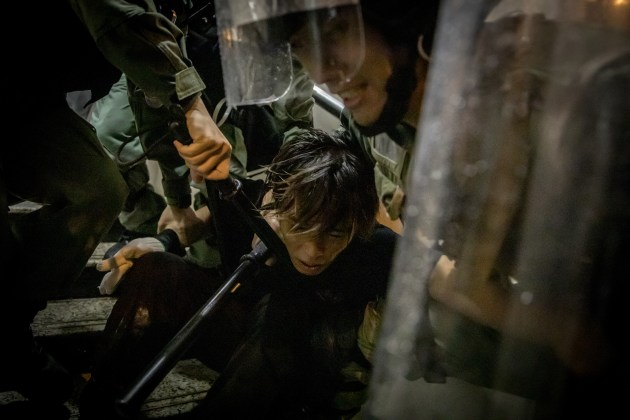© Chris McGrath. HONG KONG - AUGUST 25: A protester is tackled by police during clashes after an anti-government rally in Tsuen Wan district on August 25, 2019 in Hong Kong, China. Pro-democracy protesters have continued rallies on the streets of Hong Kong against a controversial extradition bill since 9 June as the city plunged into crisis after waves of demonstrations and several violent clashes. Hong Kong's Chief Executive Carrie Lam apologized for introducing the bill and declared it