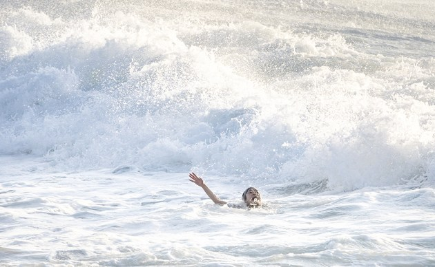 A woman screams and raises her arm as she is caught in a rip at Bronte Beach in Sydney during very rough surf conditions. © Jenny Evans