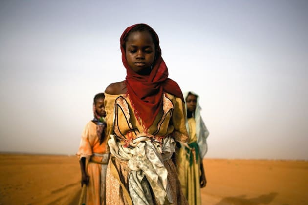 Young girls leave an IDP camp to gather firewood for their families. For some, the work will take over seven hours and lead them past government checkpoints and leave them exposed to attacks. Darfur, Sudan, 2005. © Ron Haviv/VII Photo.
