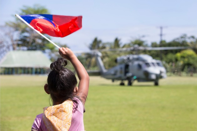 A young girl waves the Samoan flag as HMAS Choules's MR-60R Seahawk helicopter prepares to take off.