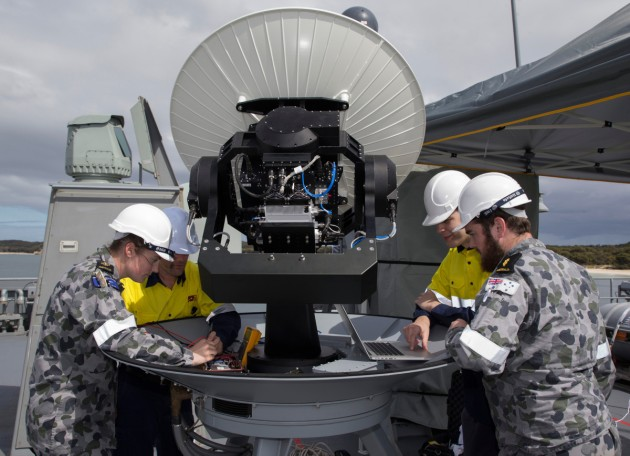 Sailors assist contractors from EM Solutions during a trial of the Tri-Band SATCOM terminal during the installation of a new Wi-Fi network.