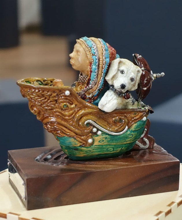 "Shari Wright, Dreamboat, Huon pine, walnut, rosewood (Tiny Treasures). ""The Dreamboat is a tiny elaborately carved boat, decorated with silver and gold-smithing and set with precious gems . The boat contains everything I would consider a perfect outing in a little boat would hold."""