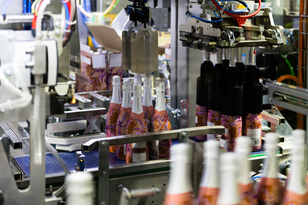 The picking head grabs and transfers bottles six at a time onto the automated partition inserter module.