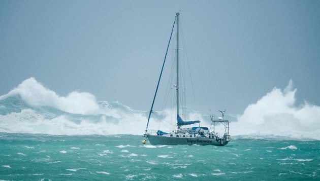 Surf pounded over the reef, the boat on the mooring beside us. Photo by Erwan Le Lann.