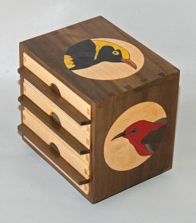 "First prize winner, Tiny Treasures, Robin Cromer, ACT. Queensland Tribute, Qld walnut veneer, silver ash. ""Maleny is pure Queensland so a tribute to the state seemed to be an appropriate for this small drawer unit. Three iconic symbols of the state were featured in marquetry: The regent bowerbird, the scarlet honeyeater and the Cooktown orchid. 