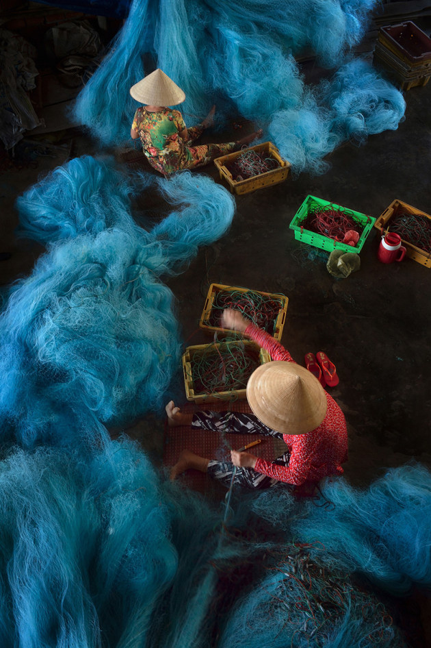 © Ly Hoang Long, Vietnam. Special Mention, Journeys & Adventures, TPOTY 2016. In Bac Lieu, one of the most popular crafts is net making. After a long fishing trip, when the boats return, the first thing the fishermen need is to have the nets mended, so it's the rush hour of any net factory. All the workers spend all the day on the net, knitting and mending as quickly as possible.