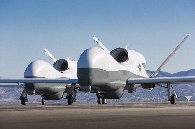 Two MQ-4C Triton unmanned aerial vehicles are seen on the tarmac at a Northrop Grumman test facility.