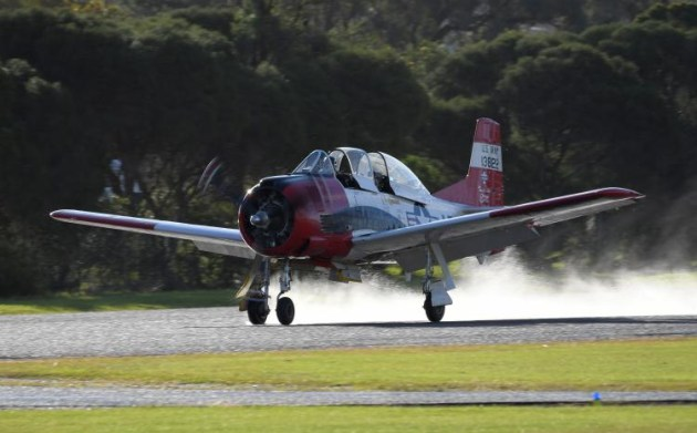 The Sunday afternoon rain left pilots facing a wet runway. Not the spray coming from this T-28 Trojan as the wheels touch the runway. (Steve Hitchen)
