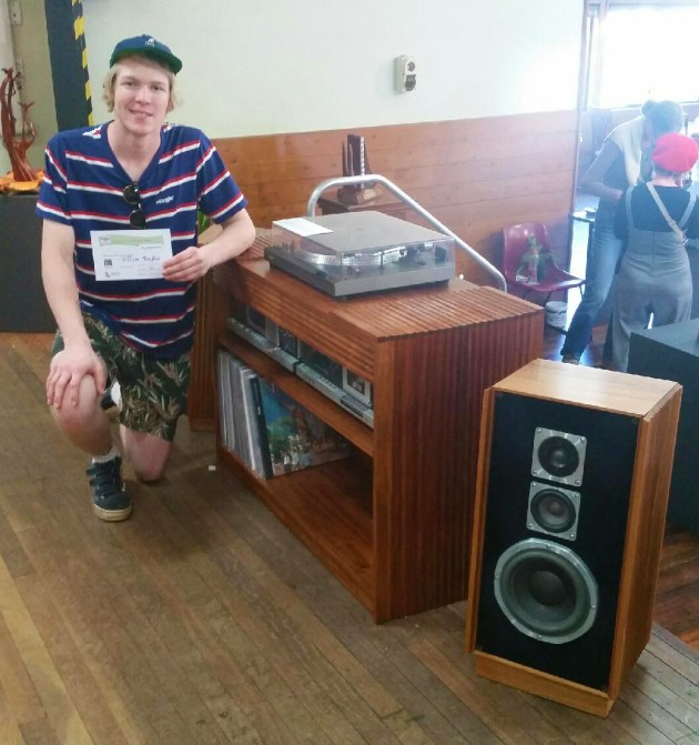 "Wootha Prize 2019 First Prize Winner (Open), William Bayliss, The Torrent Hi-Fi Cabinet and Speakers, blackwood. ""The Torrent Hi-Fi Cabinet and Speakers are made to display vintage hardware tastefully in a contemporary style. The piece is made from figured Tasmanian blackwood in both re-sawn veneer and solid timber sections with timber movement in mind. The fluting along the radius that is carried on through the top highlights the curved sides of the cabinet. Furniture as well as music both can evoke emotion and can also be enjoyed as an experience."""