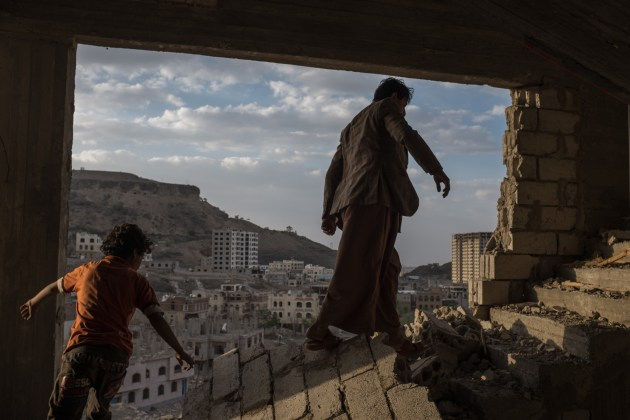 © Alex Potter. Yemeni brothers climb the broken stairs of an apartment building damaged by airstrikes in the Faj Attan district of Sana'a, Yemen, 17 August, 2015. Faj Attan mountain may have a large weapons cache inside, which, if hit by an airstrike, some assume could wipe out half the city.