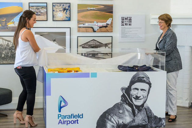 Hannah Cash (left), winner of the Peter Teakle Aviation Scholarship, and Coraine Sopru, whose late husband's Cessna is the gate guard at Parafield, unveil a display cabinet at the official opening of the Parafield Aviation Heritage Centre. (via Hughes PR)