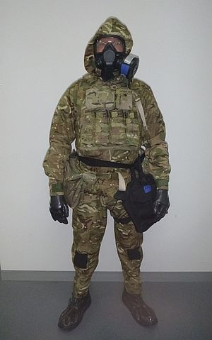 Soldier wearing the CBRN Personal Protective Ensemble consisting of the Kestrel suit, Airboss Low Burden mask, haversack, gloves and over-boots with Tier 2 Soldier Combat Ensemble (less Helmet) consisting of the Australian Defence Apparel Tiered Body Armour System - front view. Credit: Defence