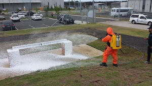 Equipment Decontamination Light backpack sprayer (Intelagard Macraw and applicator) applying a decontamination simulant foam by an operator wearing a decontamination protective ensemble consisting of a Protect Plus TF suit, Airboss over-boots and gloves and respirator (type in photo unconfirmed). Credit: Defence