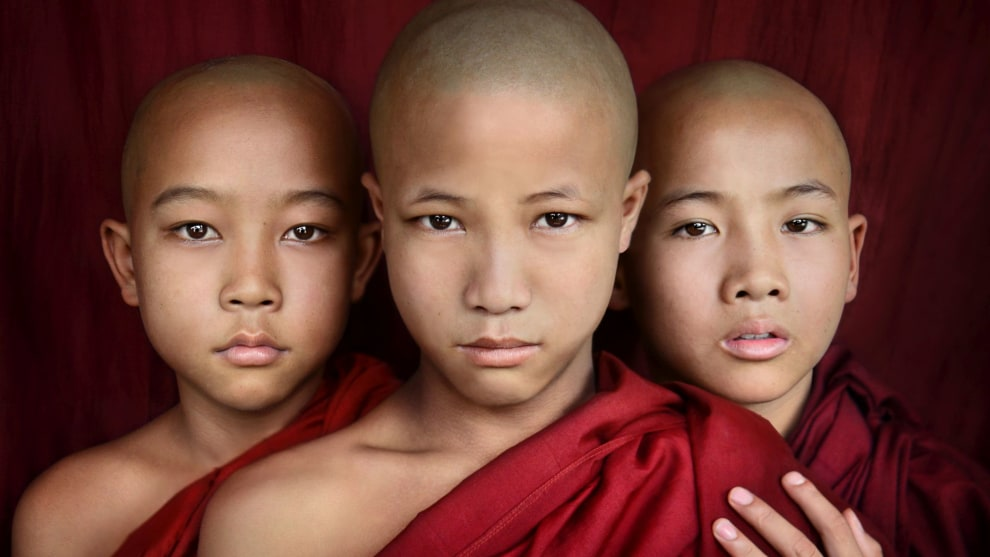 Three novice monks in Myanmar photographed in a formation that balances well and is very symmetrical. The hand on the shoulder breaks the symmetry just slightly, and adds an extra layer of emotion to the photo. Nikon D800, 24-85mm f/2.8-4 lens. 1/200s @ f7.1, ISO 500.