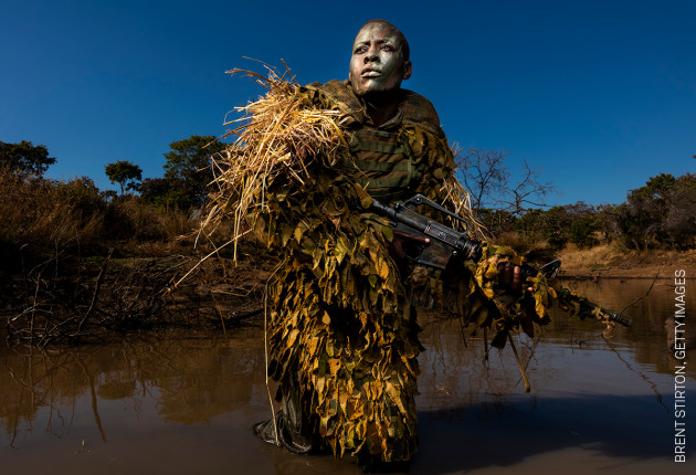 Akashinga - the Brave Ones. Petronella Chigumbura (30), a member of an all-female anti-poaching unit called Akashinga, participates in stealth and concealment training in the Phundundu Wildlife Park, Zimbabwe. © Brent Stirton, Getty Images