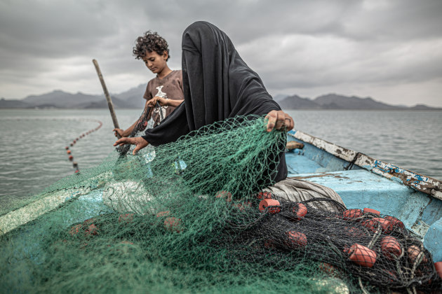 Yemen: Hunger, Another War Wound. © Pablo Tosco, Argentina. FIRST PRIZE, SINGLES. Fatima and her son prepare a fishing net on a boat in Khor Omeira bay, Yemen, on 12 February 2020.