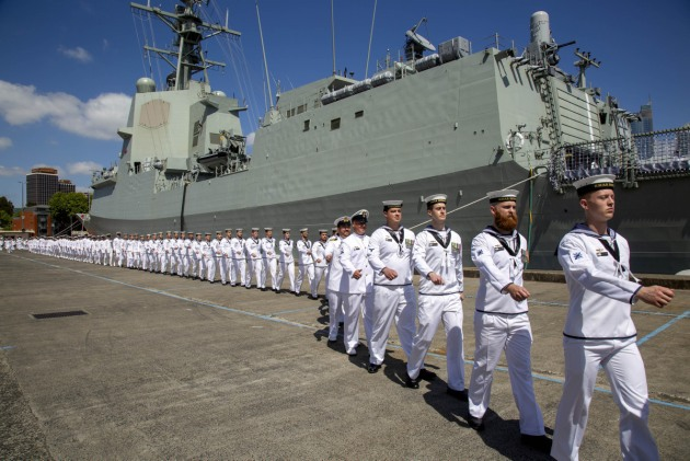 Members of the ship's company march on board during HMAS Brisbane's commissioning ceremony held at Garden Island, Sydney. Defence