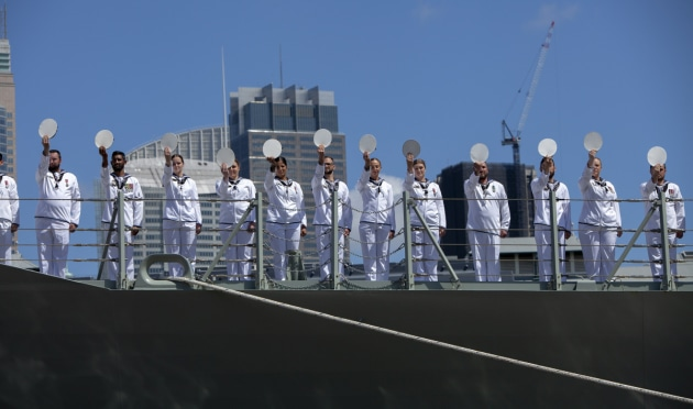 The ship's company of HMAS Brisbane line the upper decks and cheer ship during HMAS Brisbane's commissioning ceremony held at Garden Island. Defence