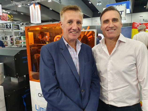 Andrew Russo, Orora (right) shows off the Limitronic in-line digital printer to PKN associate editor Wayne Robinson at AUSPACK 2019.