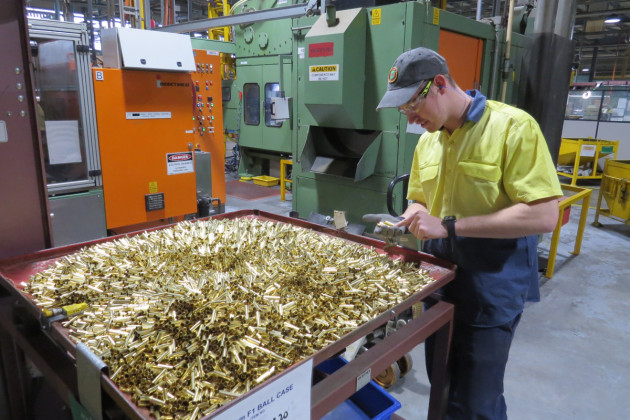 A Thales employee examines cartridge cases for 5.56mm ammunition – partway through the manufacturing process at the Benalla, VIC production line. (Defence)