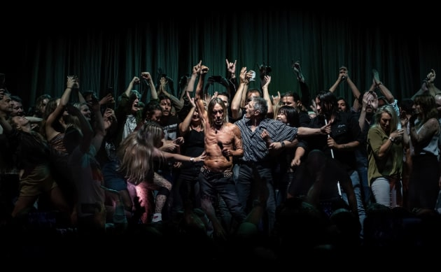 "© Antoine Veling, Australia, Winner, Open, Culture, 2020 Sony World Photography Awards. Mark 5:28. When audience members were invited on stage to dance at an Iggy Pop concert in Sydney Opera House, Australia, on 17 April 2019, it showed the warm welcome Aussies extend to overseas artists who travel long distances to reach them.  A woman's outstretched arm lunges to touch Iggy. He seems unaware of her approach as the crowd presses around him. One of Iggy's assistants, Jos (in the grey checked shirt) tries to make some space around Iggy. The scene is reminiscent of a passage from the Bible: 'Because she thought, ""If I just touch his clothes, I will be healed.""' (Mark 5:25-34, line 28). The image has been likened to religious paintings by Caravaggio, and his chiaroscuro technique. It went crazy on social media, making 40,000 people, including Iggy Pop, very happy."