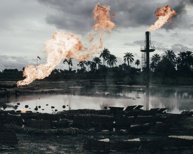© Robin Hinsch, Germany, Category Winner, Professional, Environment, 2020 Sony World Photography Awards. Natural gas flaring site, Ughelli, Niger Delta, Nigeria, from the series, Wahala. Covering 70,000 sq km (27,000 sq miles) of wetlands, the Niger Delta was formed primarily by sediment deposition. The region is home to more than 30 million people and 40 different ethnic groups, making up 7.5% of Nigeria's total land mass. It used to boast an incredibly rich ecosystem, containing one of the highest concentrations of biodiversity on the planet, before the oil industry moved in. The Nigerian department of petroleum resources estimates that 1.89 million barrels were spilled in to the Niger Delta between 1976 and 1996. What's more, a report from the United Nations suggests there have been a total of 6,817 spills between 1976 and 2001, amounting to some three million barrels of oil.