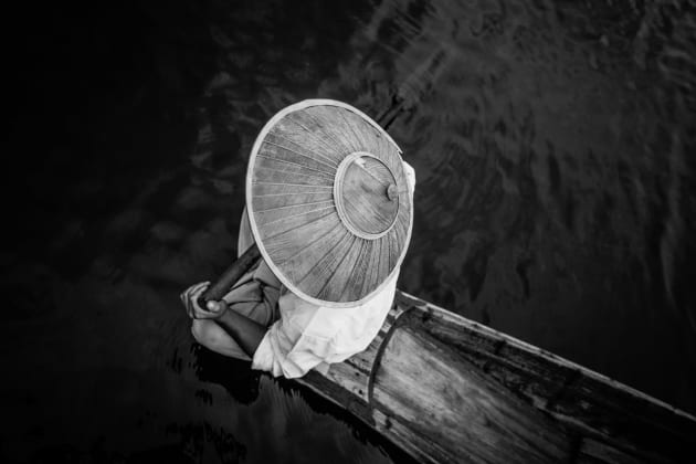Fisherman sitting on his wooden boat on inle lake in myanmars shan state by