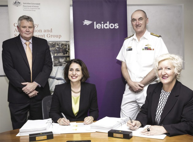 MD Leidos Australia Christine Zeitz (L) and Assistant Secretary Alison Petchell (R) sign the sustainment of the ADF's Joint Command Support Environment contract watched by Paul Chase of Leidos and RADM Tony Dalton.