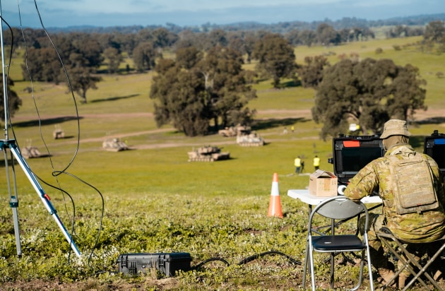 An Australian soldier monitors an autonomous Australian Army M113AS4 Armoured Personal Carrier enhanced as an Optionally Crewed Combat Vehicle (OCCV) as it manoeuvres with larger M1A1 Abrams tanks during a demonstration at Puckapunyal Army Base. (Defence)