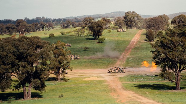 Australian Army M1A1 Abrams tanks (top and bottom) fire at an enemy defensive position as autonomous Australian Army M113AS4 Armoured Personal Carriers enhanced as Optionally Crewed Combat Vehicles (OCCV) work as a team during a demonstration at Puckapunyal Army Base. (Defence)