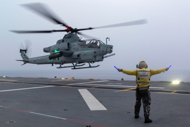 Leading Seaman Aviation Support Jamie Kennedy marshals a Marine Corps AH-1Z Viper helicopter aboard HMAS Adelaide.