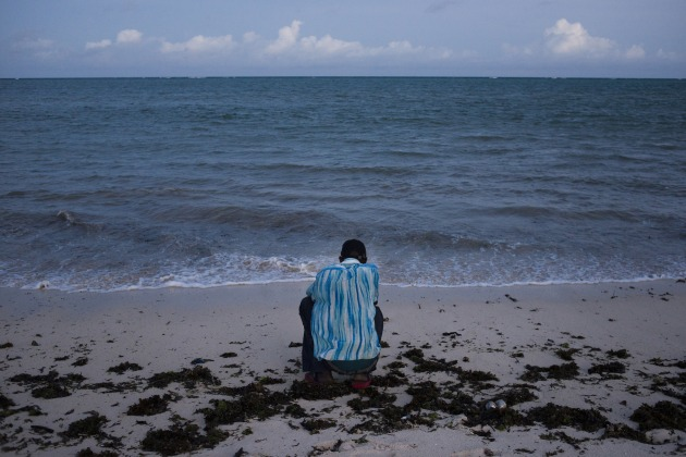 © Alex Potter. M looks out to sea on the south coast of Mombasa, Kenya on April 11, 2016. M returned to Mombasa after defecting from Al Shebaab. He spent over five years in Somalia, and fears every day the police will take him from his family in Mombasa.