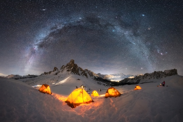 """Base Camp"" – Giulio Cobianchi, Dolomites – Italy. I love shooting the Milky Way throughout all 12 months of the year. I must admit that during the winter season, it fascinates me even more, probably because the Milky Way has cooler colors that combine perfectly with the snow, and also because shooting under these conditions is much more challenging."