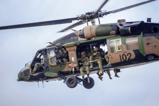 Soldiers from 2 Commando on board a 6th Aviation Regiment Black Hawk helicopter.