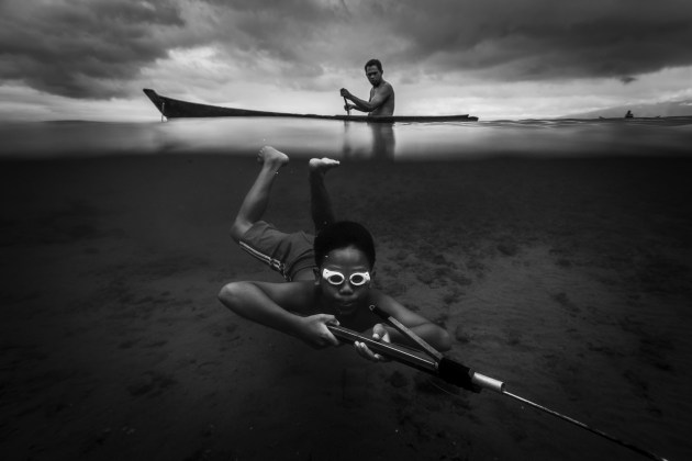 3rd Prize Winner, Water. Buchari Muslim Diken, Indonesia Octopus Hunter. A portrait of a child looking for an octopus around the coast of a fishing village in Ambon, the Maluku islands. The lives of children here rely on the sea, where they are used to doing everything themselves from a very young age.
