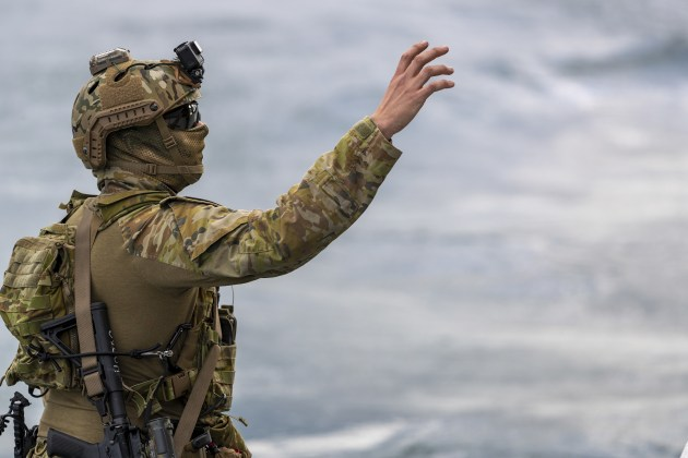 A special forces soldier from 2nd Commando Regiment reaches out for the rope to support other soldiers fast-roping onto a Sydney ferry from an Army MRH-90 Taipan.