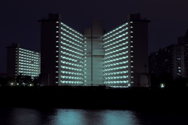 Toshima 5-chome Danchi. The illuminated form of a danchi across the Sumida River. © Cody Ellingham.
