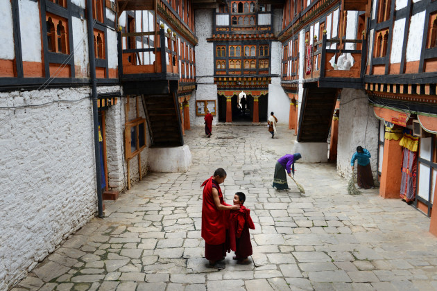 Life in the Dzong. After the viewer focuses on the monks adjusting their robes in the centre of this Dzong fortress courtyard in Bhutan, there are more people to then discover throughout the scene. Nikon D800, 24-70mm f/2.8 lens @ 31mm. 1/320s @ f8, ISO 1250.