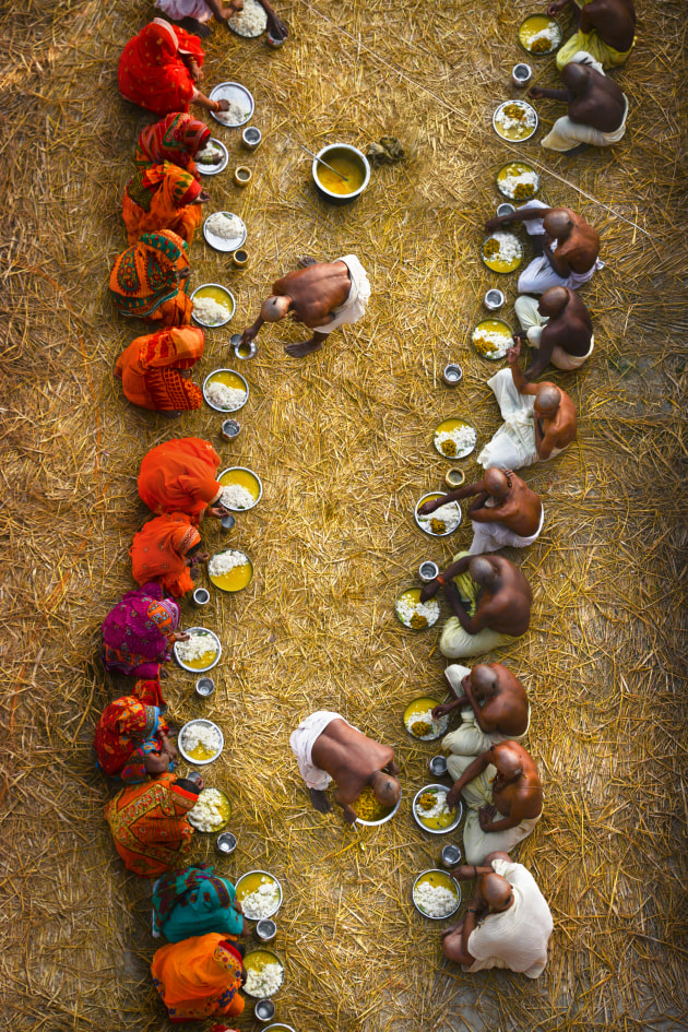 Pilgrims Eating Together. This was photographed from a large bridge at the Kumbh Mela Festival in India, I saw these lines of pilgrims eating below and photographed them from above looking straight down, zooming in to 135mm. By framing the two lines equally with similar spacing on either side, a pattern of two lines is created which provides visual interest. Nikon D800, 28-300mm f/3.5-5.6 lens @ 116mm. 1/250s @ f8, ISO 400.