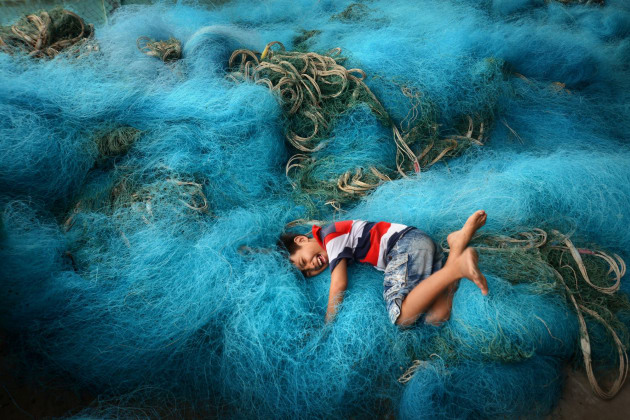 Boy playing in fishing nets in the Mekong Delta region of Vietnam. I found the background of the fishing nets and encouraged the boy to jump into them, and I even demonstrated the idea to him by doing it myself. I noticed that the nets were in a good location that was undercover yet near an opening to the sky for strong, even light, and would make for interesting patterns in a background to this playful environmental portrait taken in Vietnam. Nikon D800, Nikon 24-85mm f2.8-4 lens. 1/250s @ f8, ISO 500.