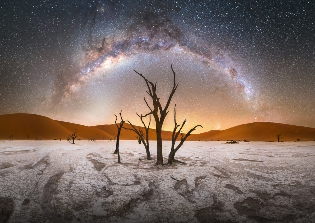 """Deadvlei"" – Stefan Liebermann, Namib-Naukluft National Park – Namibia.The trees in Deadvlei have been dead for over 500 years. Located in Namib-Naukluft Park in Namibia, these saplings grew after local rivers flooded because of severe rainfalls, but died after the sand dunes shifted to section off the river. High above and far in the distance, the band of our Milky Way galaxy forms an arch over a large stalk in this night panorama image."