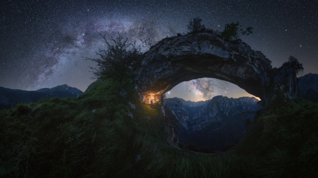 """Double Arch"" – Pablo Ruiz García. ""Picos de Europa"" – Spain. This spectacular arch-shaped rock formation is located in ""La Hermida"" gorge, in the Picos de Europa mountain range in Spain. At first, my initial idea was to capture the galactic center inside the arch, but finally, I decided to shoot the two arches overlapped at this time of the year (late spring) when the Milky Way is still not too high in the sky."