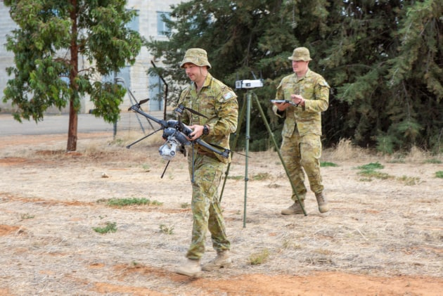 No. 3 Security Forces Squadron Leading Aircraftman Rhys Mitting (left) and Chaddyn Bray prepare the drone for operation from an airborne C-130J Hercules.