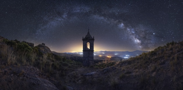 """Enchanted Monastery"" – Ramón Morcillo, Ávila – Spain. The idea of shooting an old monastery under the Milky Way in the Spanish mountains was just hanging around my head for months. I was fascinated by the idea of planning this image; having the Milky Way arch above the ancient and lonely bell tower. The monastery was an Augustinian convent founded in 1504 and called the ""Monastery of Our Lady of the Crag"". A few hundred miles drive followed by a long walk and a challenging climb and bushwhack ended in this beautiful and magical place where I could capture our galaxy arch."