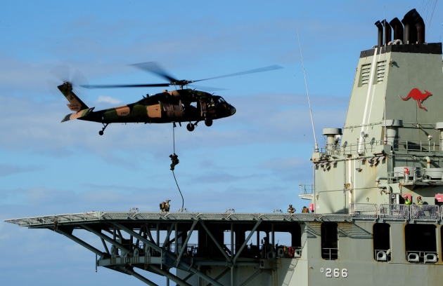 A Black Hawk helicopter hovers over the flight deck to enable Army special operations soldiers to fast-rope onto HMAS Sirius.