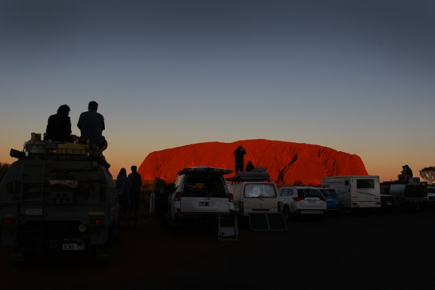 Visitors line up their vehicles to take in the sunset view of Uluru on August 12, 2019 in the Uluru-Kata Tjuta National Park, Northern Territory. The Uluru-Kata Tjuta National Park board unanimously decided the climb up Uluru will close permanently on October 26, 2019. According to Parks Australia, Uluru has welcomed 244,075 visitors this calendar year, an increase of 18.7%. Sacred to the Yankunytjatjara and Pitjantjatjara people, climbing Uluru is strongly discouraged for its cultural significance and concerns for peoples' safety. Over 30 people have died and numerous injured while attempting the steep ascent, less than 20 percent of park visitors take part in the climb. Image: Lisa Maree Williams/Getty Images.
