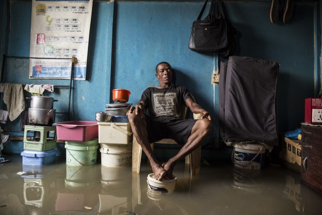 Category: Mental Health (series). © Nyancho NwaNri. Going Under,  Lagos, Nigeria, 2019. This neighbourhood on the bank of the Lagos lagoon suffers annual flooding – more severely and for longer, as climate change raises sea levels. Apart from the physical damage and the risk of water-borne diseases, there comes a threat to mental health. A resident sits in his room with his feet up on a paint bucket to avoid the floodwater.