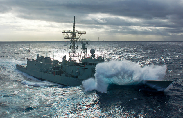 A 2013 photo of HMAS Melbourne as the crew prepares to connect fuel hoses with HMAS Sirius in a high sea state.