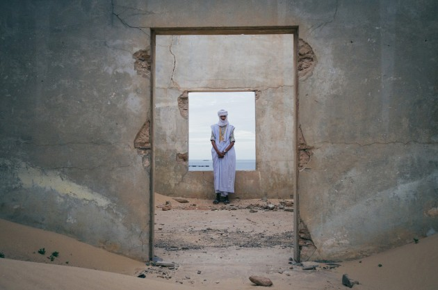 © Jody MacDonald. A Mauritanian man leans against the window frame inside an old abandoned building that is slowly being taken over by the Sahara desert.